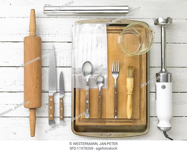 Kitchen utensils: a rolling pin, knives, cutlery, a pastry brush and a hand blender