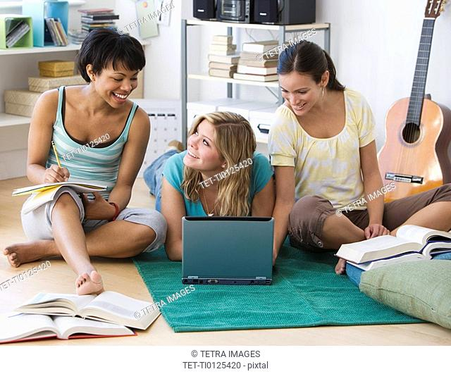 Multi-ethnic women studying on floor