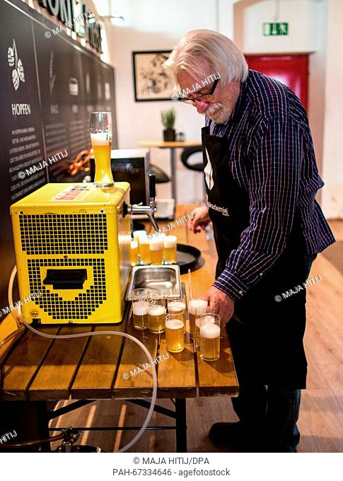 . Course instructor Gerd Ruhmann fills glasses during a beer brewing