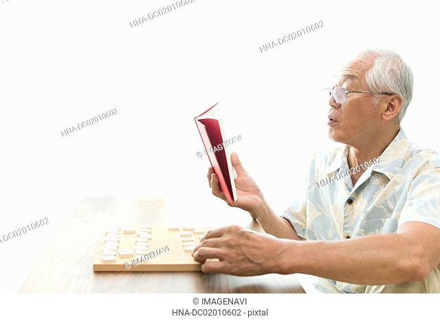 A senior man playing a shogi problem