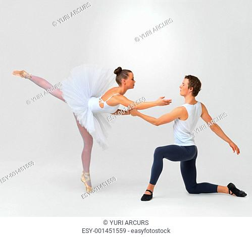 Full length of two beautiful ballet dancers performing against white background - copyspace