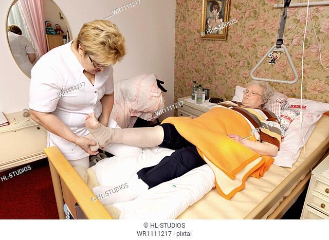 Geriatric nurse bandaging leg of old woman