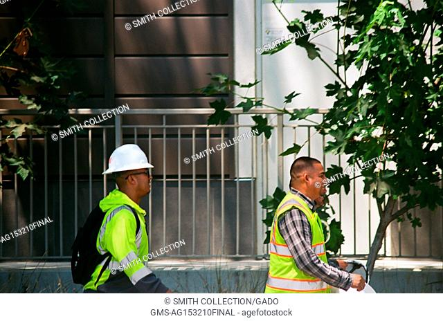 Construction workers with hard hats and high visibility vests walk near the construction zone at the Apple Park, known colloquially as 'The Spaceship'