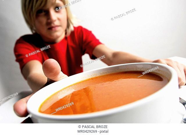 Portrait of a boy holding a bowl of soup