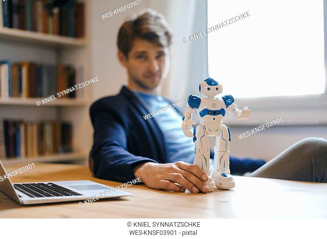 Man sitting at table with robot