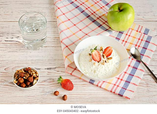 Healthy breakfast of cottage cheese with strawberries, nuts and apple on white wooden background. Healthy food, Detox, Diet, Clean Eating or Vegetarian concept