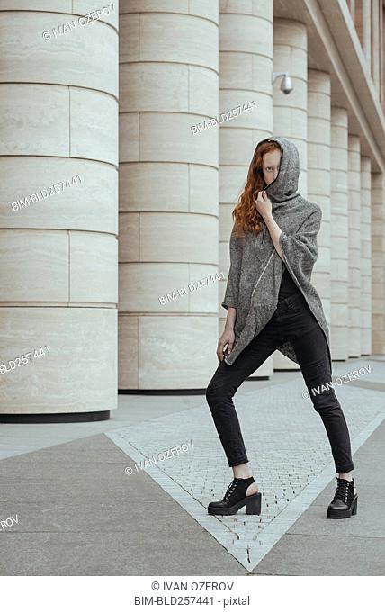Caucasian woman hiding face behind hood near pillars