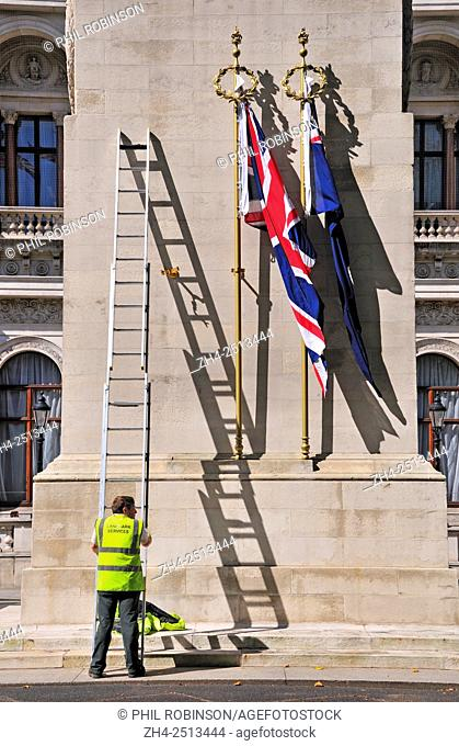 London, England, UK. Men changing the flags on the Cenotaph in Whitehall