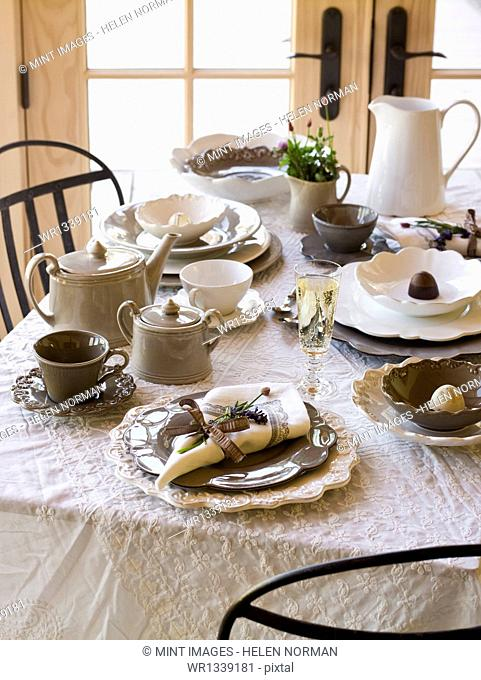 A table laid for a meal, with a white table cloth and traditional white china, table napkins, and cutlery