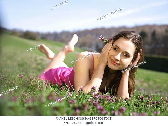 Young brunette woman lying on a meadow grass landscape flowers lying nature park sun pink