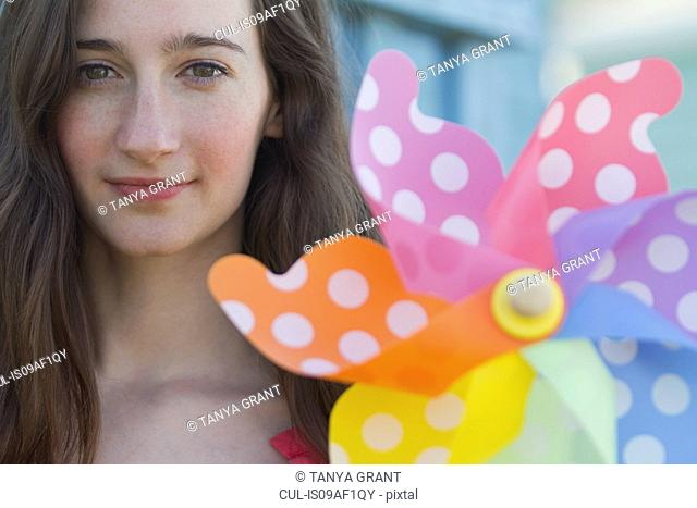 Portrait of young woman holding paper windmill