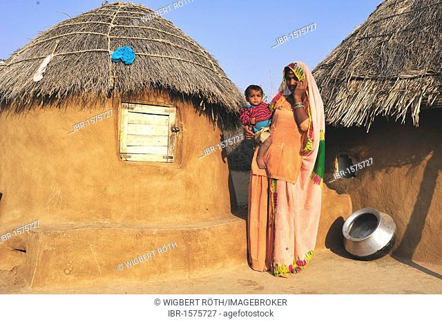 Mother with her child on her arm in front of house, Thar Desert, Rajasthan, India, Asia
