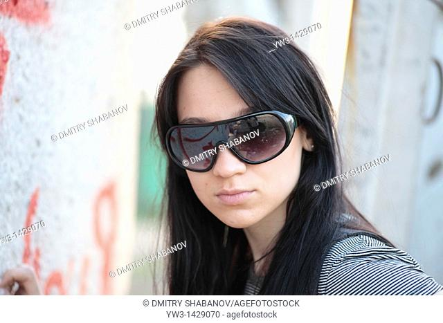 beautiful brunette outdoor portrait against street graffiti