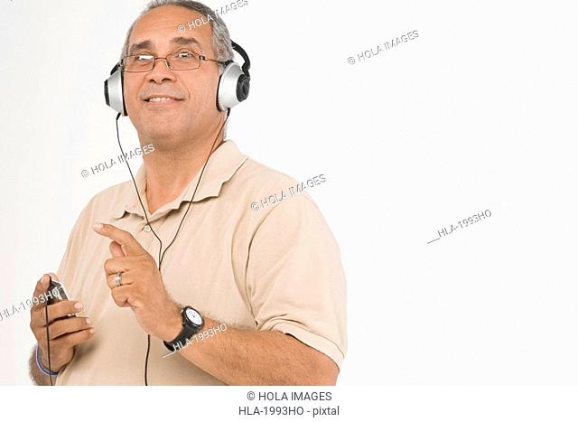 Portrait of a mature man listening to an MP3 player