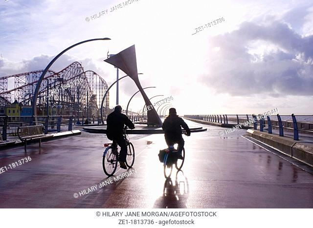 Blackpool Lancashire England South Promenade Two cyclists passing Swivelling Wind Shelter sculpture with Big One roller coaster to left