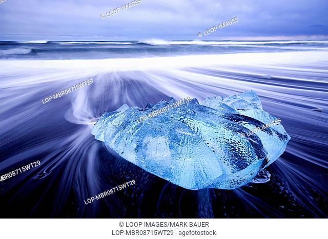 Waves washing around a small iceberg on the beach at Jokulsarlon in Iceland