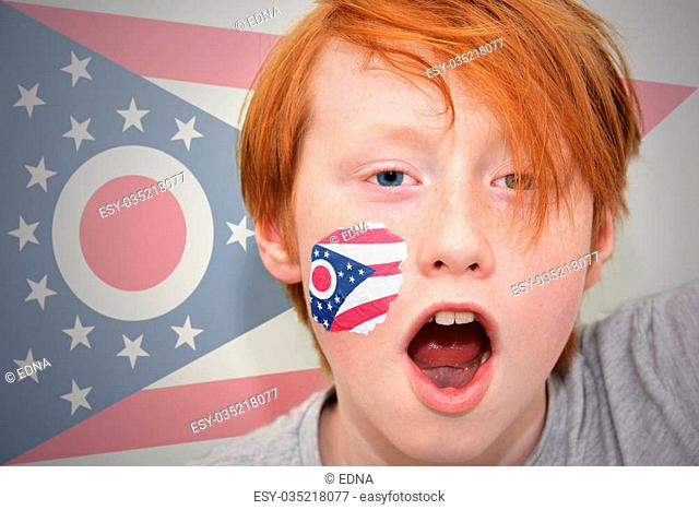 redhead fan boy with ohio state flag painted on his face. on the ohio state flag background