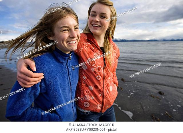 Two young women walk arm in arm at Bishop's Beach in Homer, Alaska