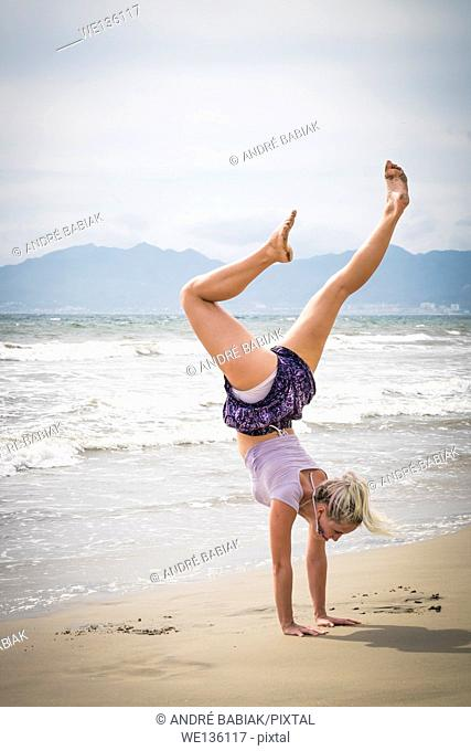Young woman performing a hand stand at a beach. Riviera Nayarit, Pacific Coast, Mexico