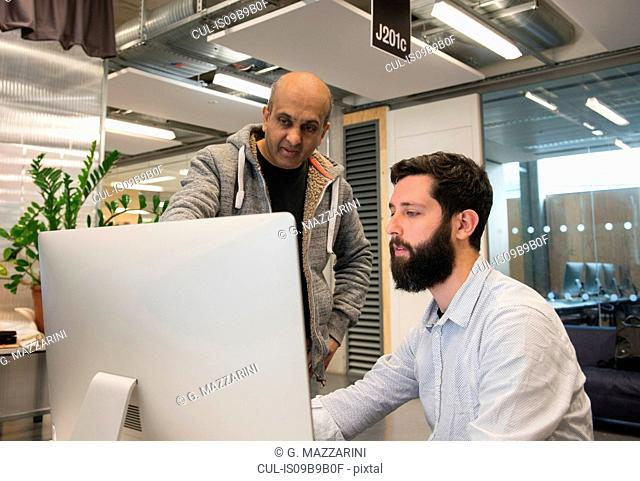 Colleagues in office looking at computer monitor