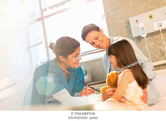 Smiling female nurse using stethoscope on girl patient in hospital room