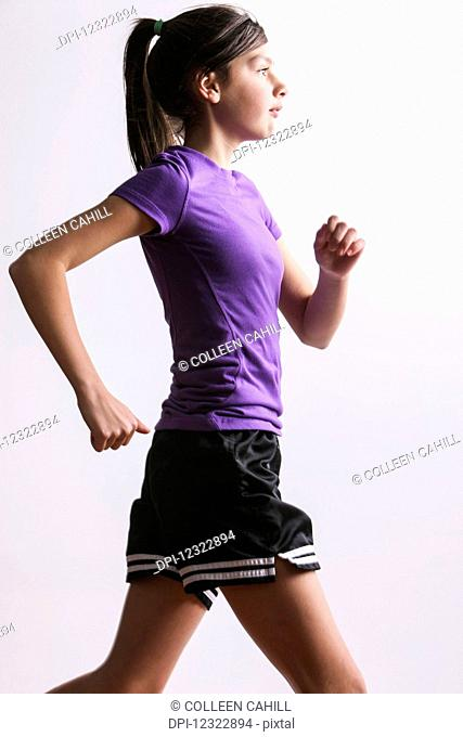 A teenage girl running against a white background; Oregon, United States of America