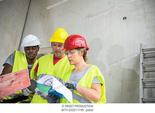 Construction workers with architectural plan at building site