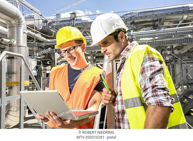 Engineer with his colleague in meeting with laptop at geothermal power station, Bavaria, Germany
