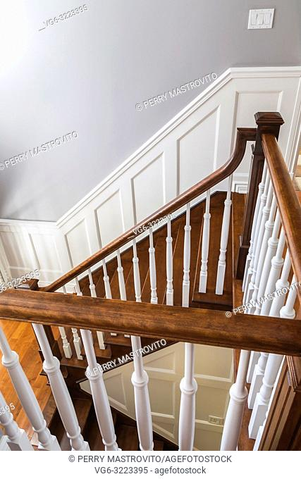 Cherry wood staircase and railings with white spindles on the upstairs floor inside a contemporary cottage style home