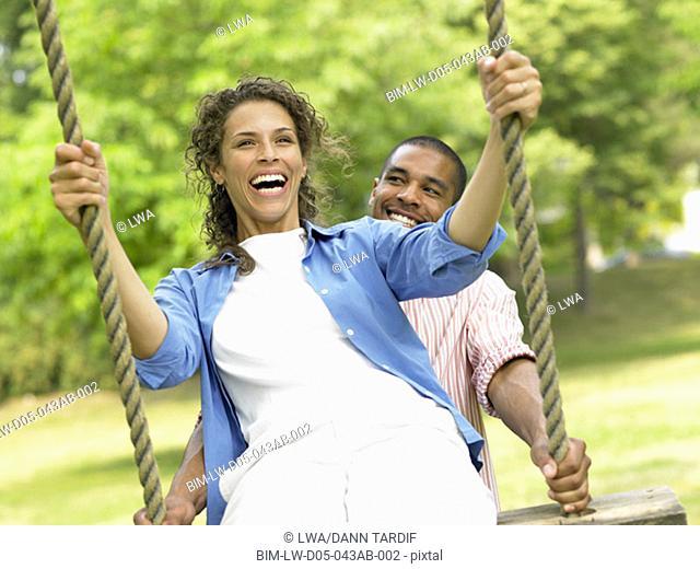 Couple swinging on swing