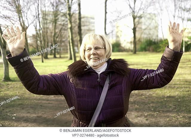 happy senior woman with arms up outdoors in park, in Cottbus, Brandenburg, Germany