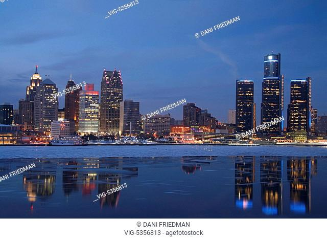 Skyline of downtown Detroit, Michigan, USA seen after sunset. Ice can be seen floating in the Detroit River. Detroit is known as The Motor City, The D, Motown