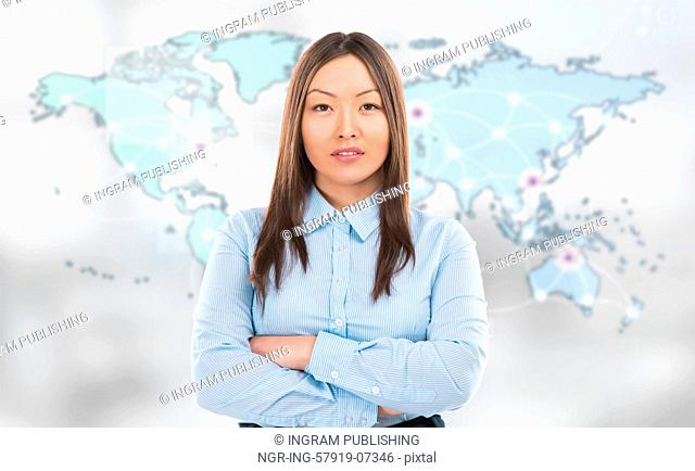 Portrait of young woman standing in front of big world map and looking at camera. Server locations and actual online connections are displayed on virtual map