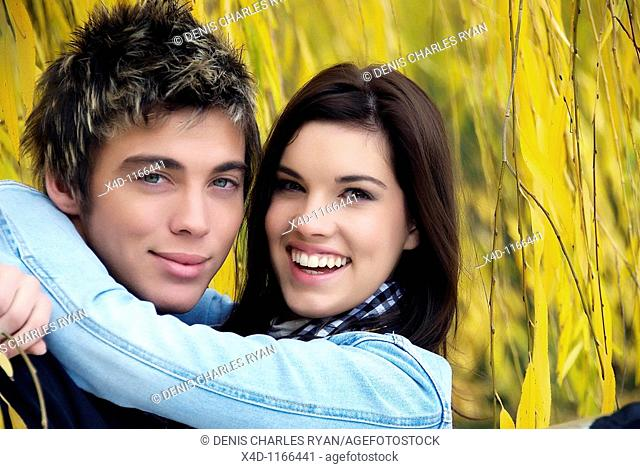 Casual Male and Female, cuddling under a weeping willow in the fall in casual attire