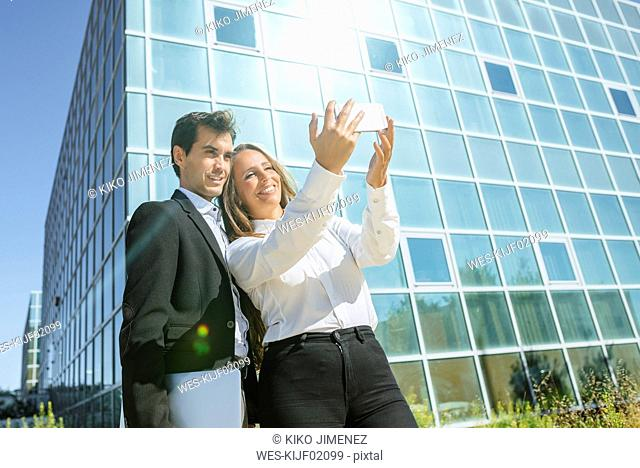 Smiling businesswoman and businessman taking a selfie outside office building