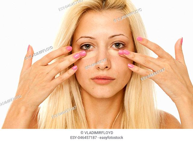 A young blonde woman applying concealer under her eyes