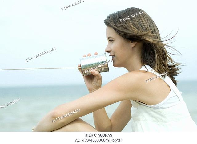 Teen girl talking into tin can phone, profile