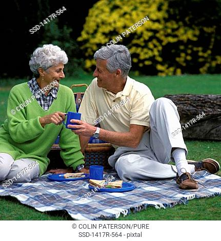 Senior couple sitting together outdoors at a picnic