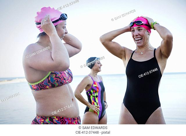 Smiling female open water swimmers adjusting swimming caps at ocean