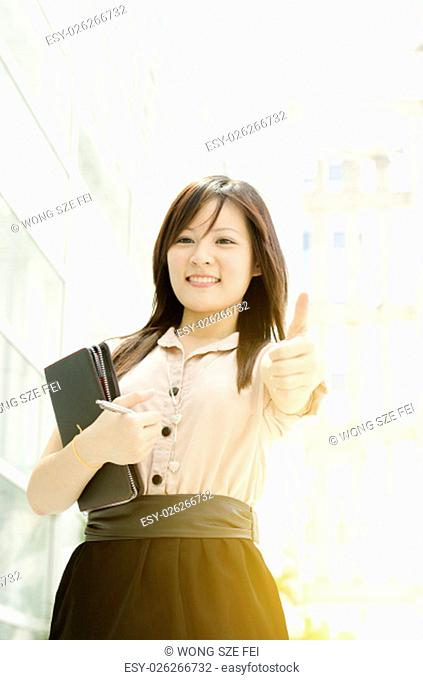 Young Asian business woman smiling and thumb up at an office environment, beautiful golden sunlight at background