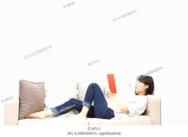 Young Japanese woman reading book on the sofa