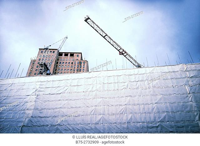 Building under construction (rehabilitation) with cranes and a large protection fence. Shell Centre, Waterloo, London, England