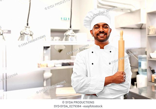 indian chef or baker with rolling-pin at kitchen