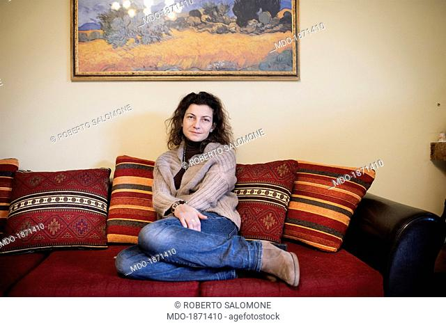 Smiling woman curled up on the couch. Sessa Aurunca (Italy), 2nd February 2014