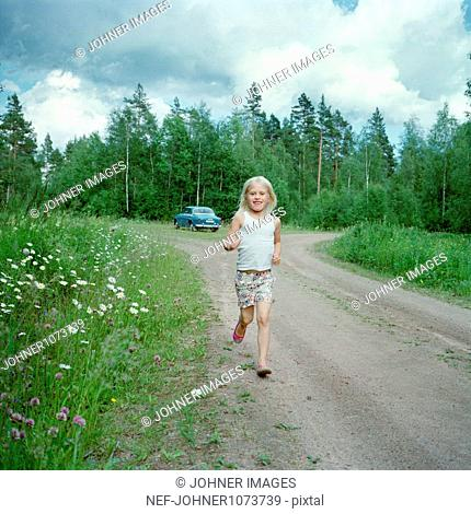 Girl running through dirt track, car in background