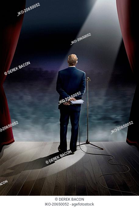 Businessman standing on stage holding microphone behind back