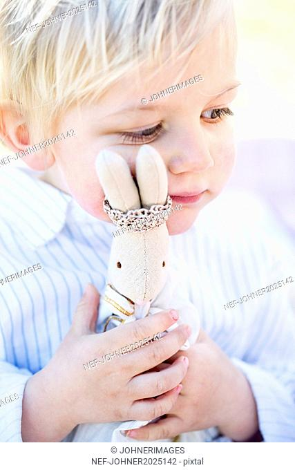 Boy hugging rabbit toy
