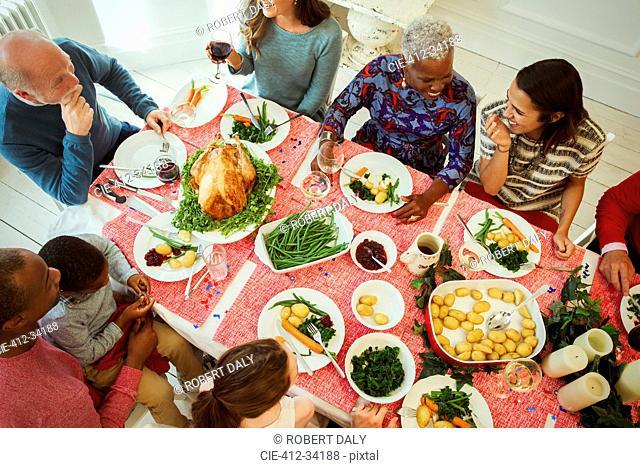 Overhead view multi-ethnic multi-generation family enjoying Christmas dinner at table