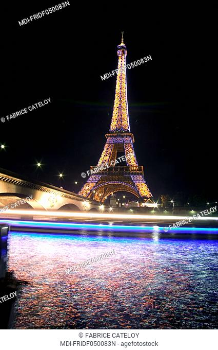 The Eiffel tower at night from the quays of the Seine - A cruising boat illuminates the river