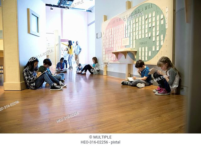 Children writing in notebooks in science center